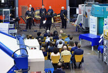 An orchestra performing in a manufacturing hall